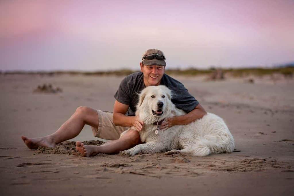 man and dog enjoy sunset on beach in Rockaway, Oregon