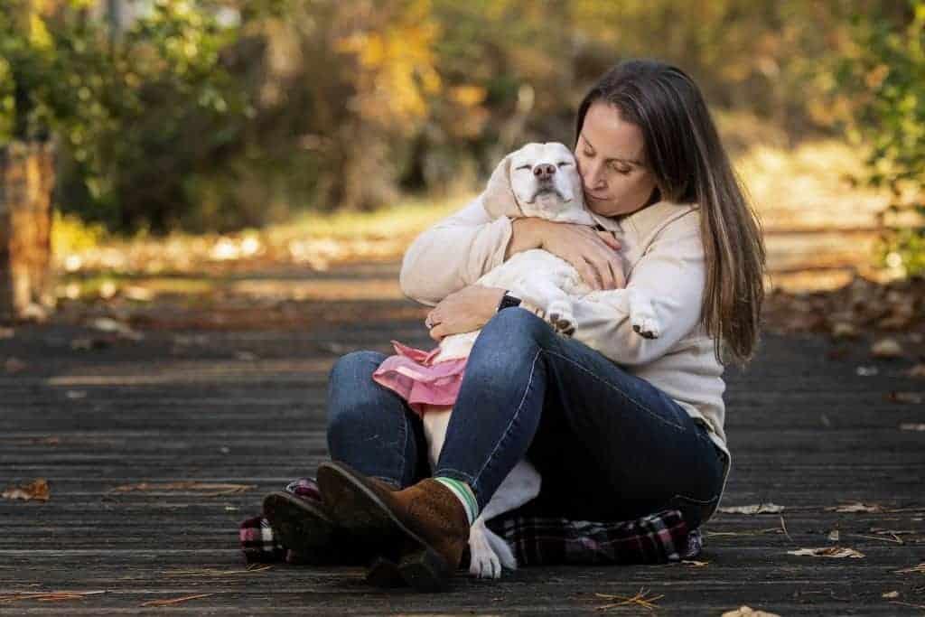 dog owner hugs her beagle