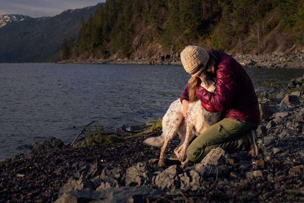 Woman hugs her dog during a hike at Evans Landing in North Idaho