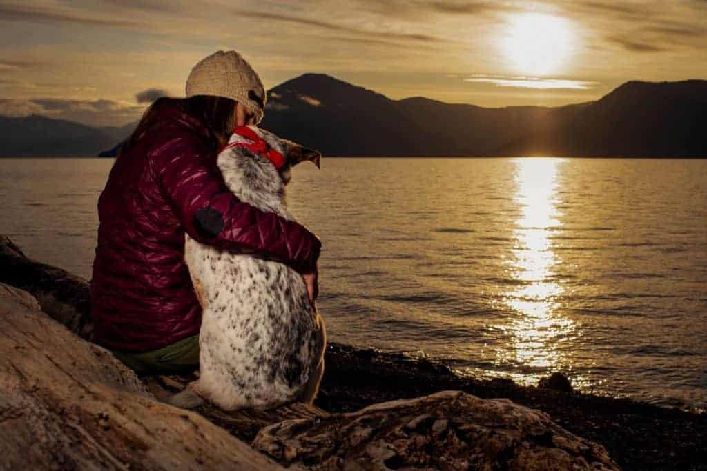 woman and dog enjoy sunrise at Evans Landing in North Idaho