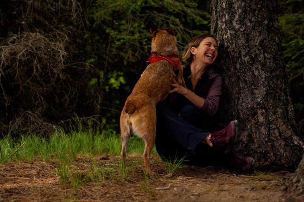 woman and dog take a break while hiking at Gold Hill in Sagle, Idaho