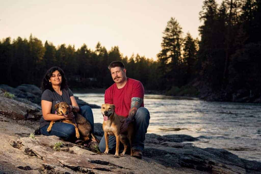 couple with dogs pose for family photo session on Spokane River