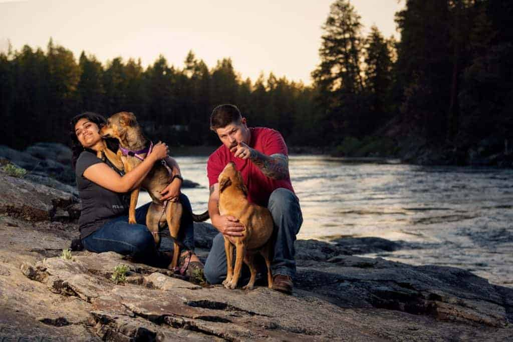 couple tries to convince dogs to look at camera during dog photography session at Post Falls