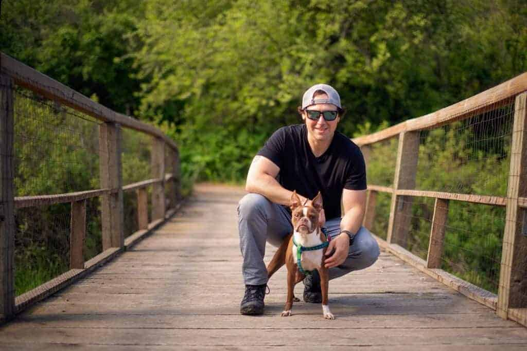 man and his boston terrier on a walking bridge at Farragut State Park